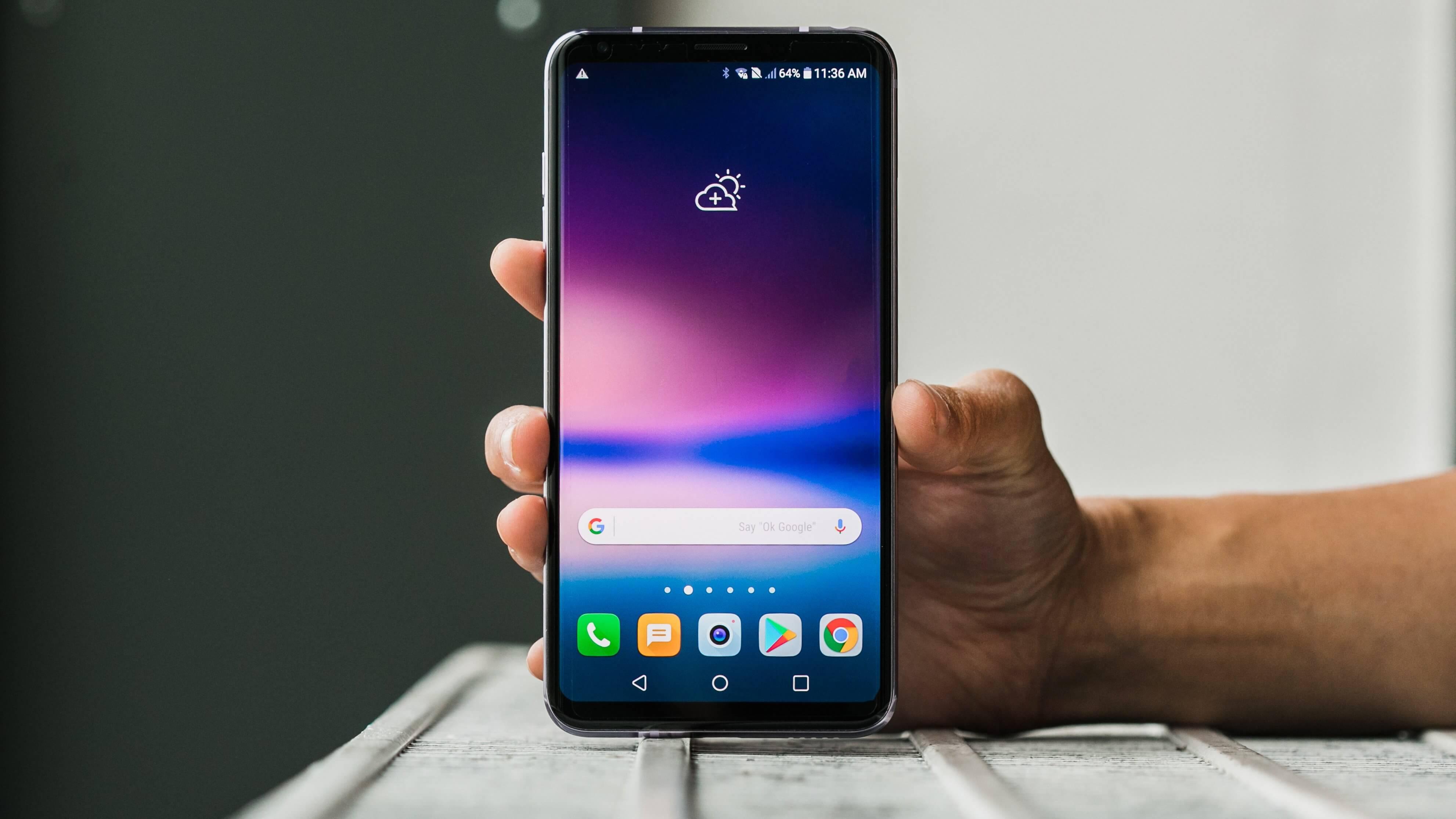Uma pessoa segurando o celular LG V30, lançado em 2017 pela empresa