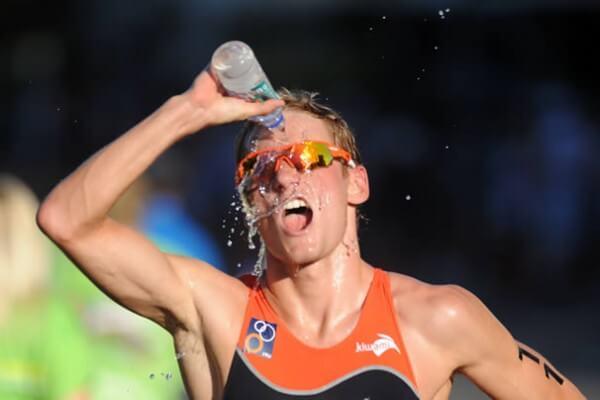 Corredor de maratona se hidratando com copo de água