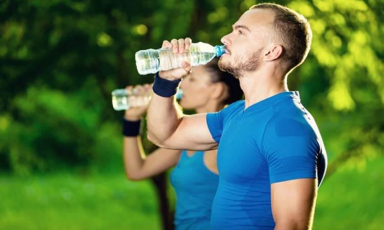 Pessoas tomando água em parque aberto