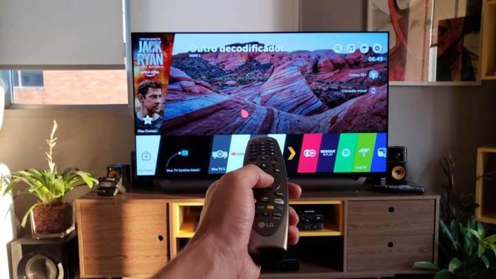 Pessoa apontando controle remoto para TV