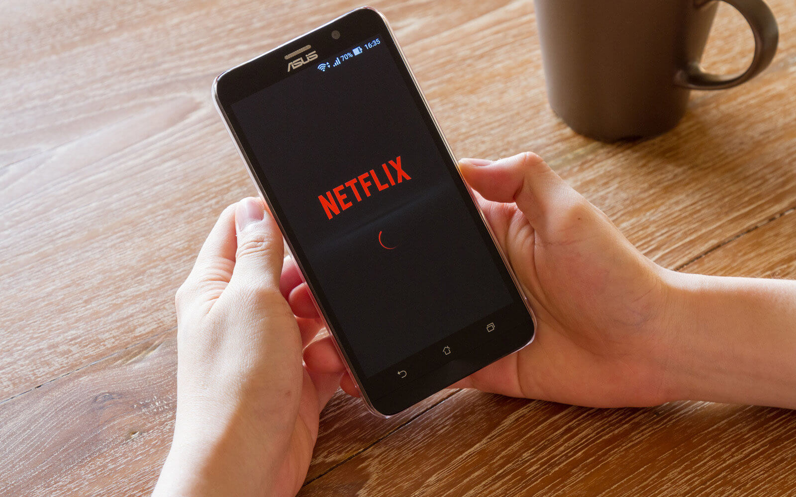 man hand holding screen shot of Netflix application