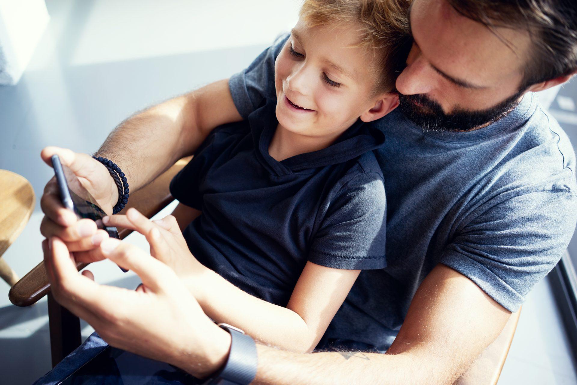 Pai e filho jogando smartphone