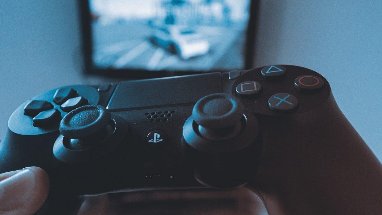 mão segurando um controle de PS4