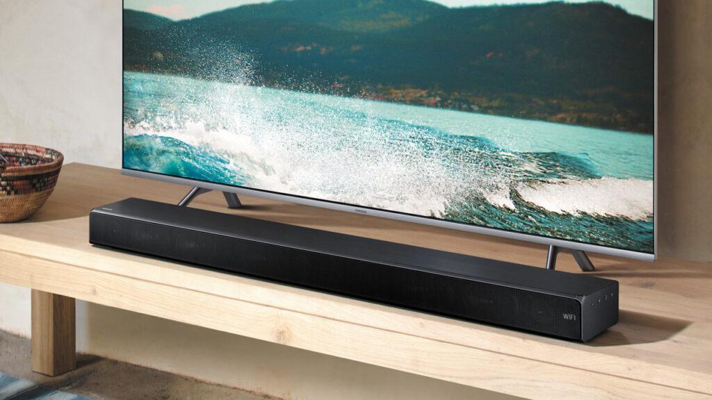 Soundbar embaixo de tv com imagem de um mar azul esverdeado