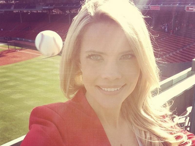 Mulher tirando selfie com uma bola de beisebol atrás