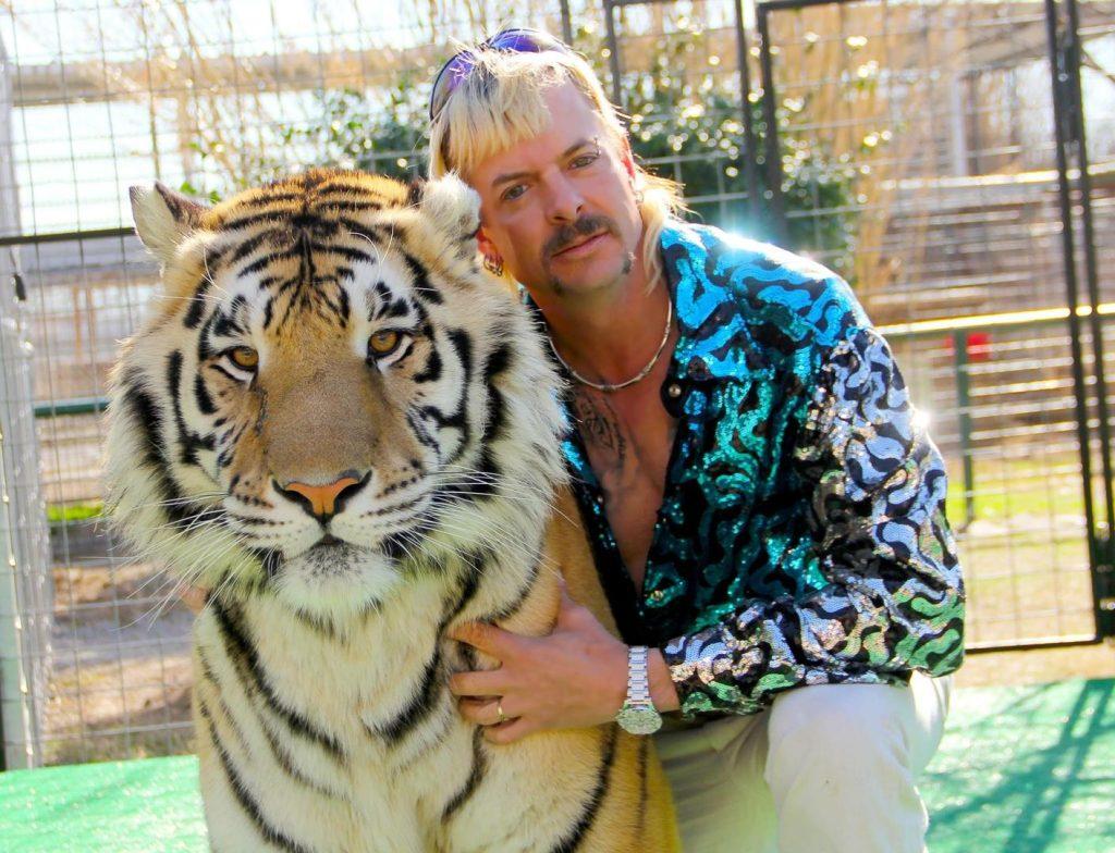 Um homem, à direita, abraça com um braço um tigre. Os dois, de frente, olham para a câmera.