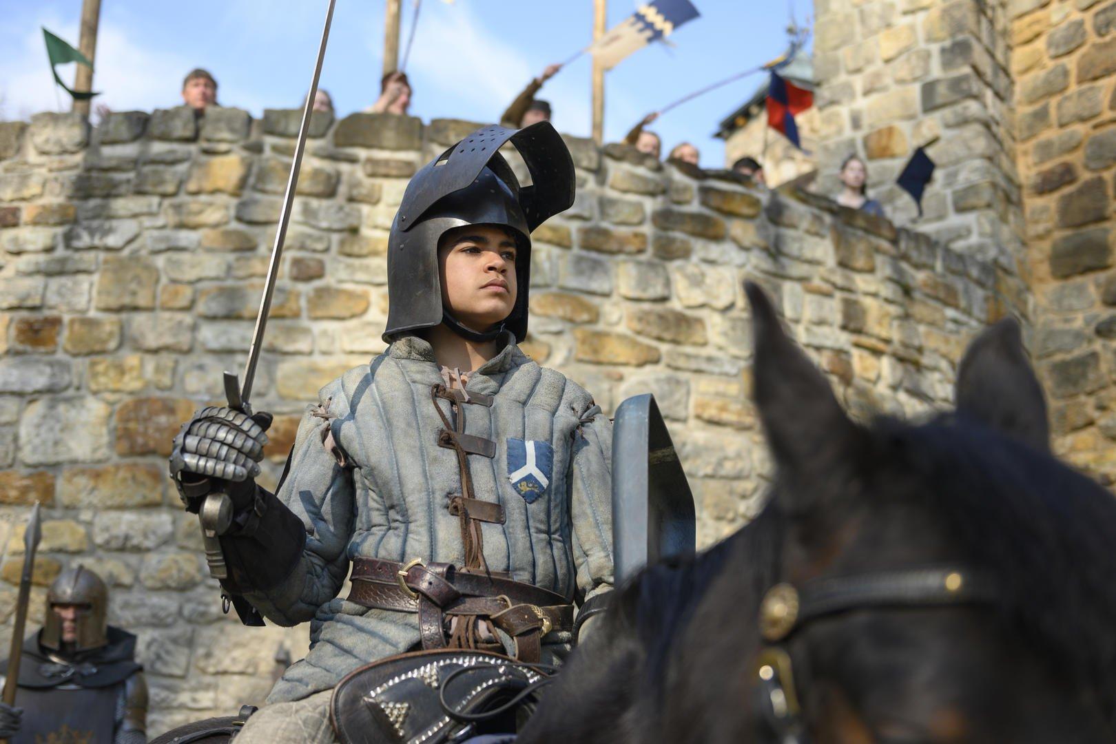 Cena de Carta ao Rei, uma das estreias da Neflix em março. Nela, um jovem está sentado segurando uma espada, sentado em um cavalo, em frente a um castelo.