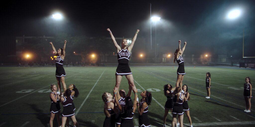 Nessa cena de Não Provoque, um grupo de animadoras de torcida pratica uma apresentação em campo de futebol americano durante a noite.