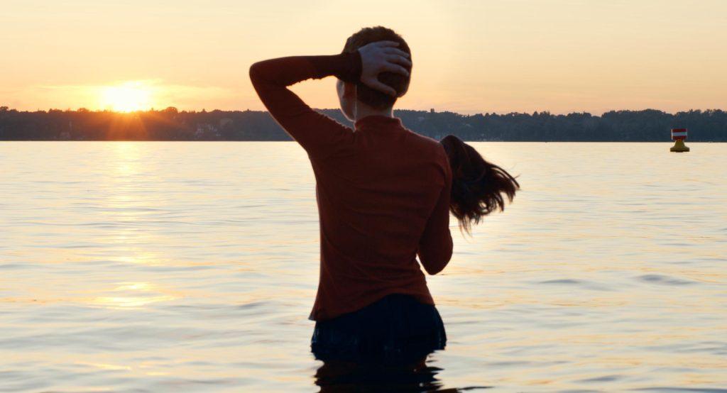Uma jovem está em pé dentro de um rio, com a água chegando quase à altura da cintura, de costas para a câmera. Ela olha o horizonte.