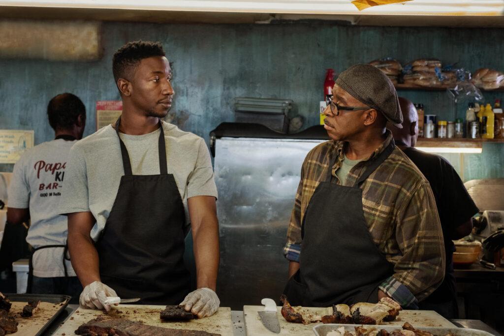 Pai e filho se encaram. Ambos estão em frente a uma mesa cortando carnes.