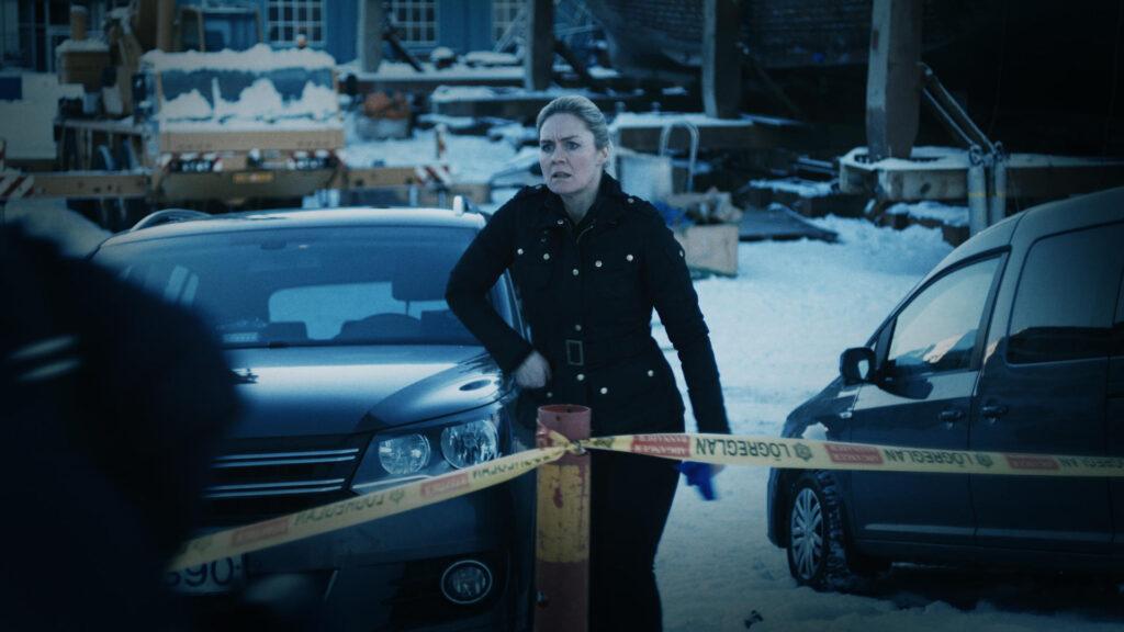 Essa cena mostra a detetive protagonista chegando a um local de isolado com uma fita pela polícia.