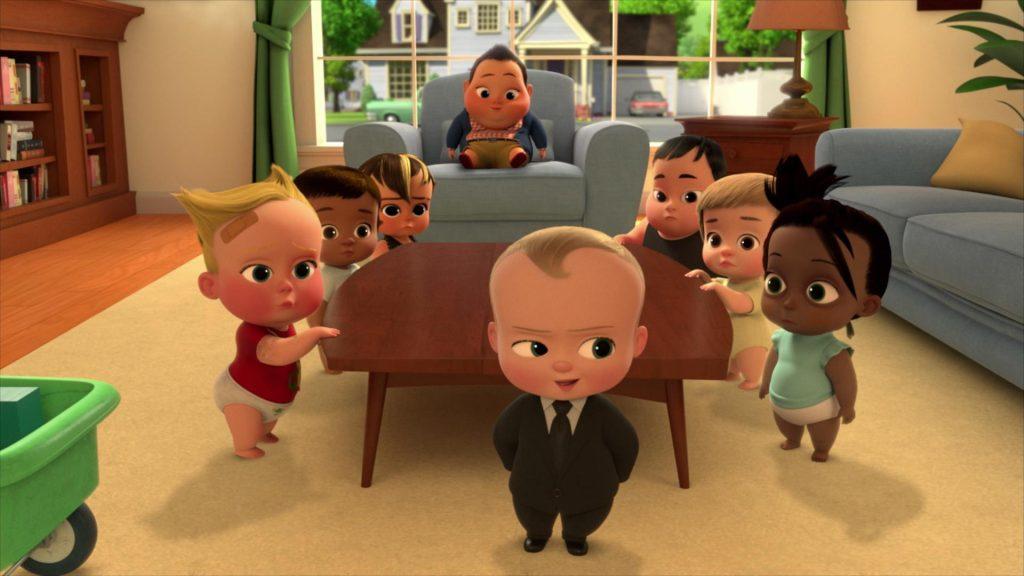 Vários bebês reunidos na sala de uma casa. Todos olham para o bebê protagonista.