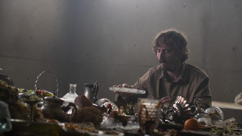 Um homem olha para um prato transparente vazio. Em cima da mesa, em frente a ele, vários objetos de mesa bagunçados.