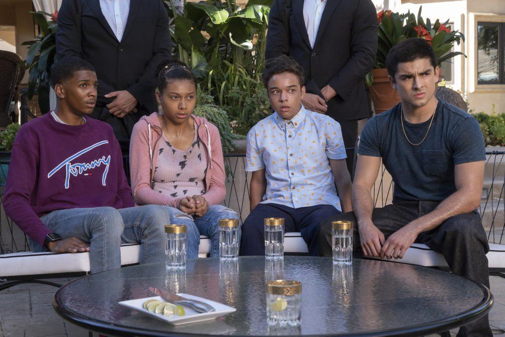 Trecho de On My Block com 4 jovens sentados em torno de uma mesa. Eles olham com tensão para alguém que está chegando.