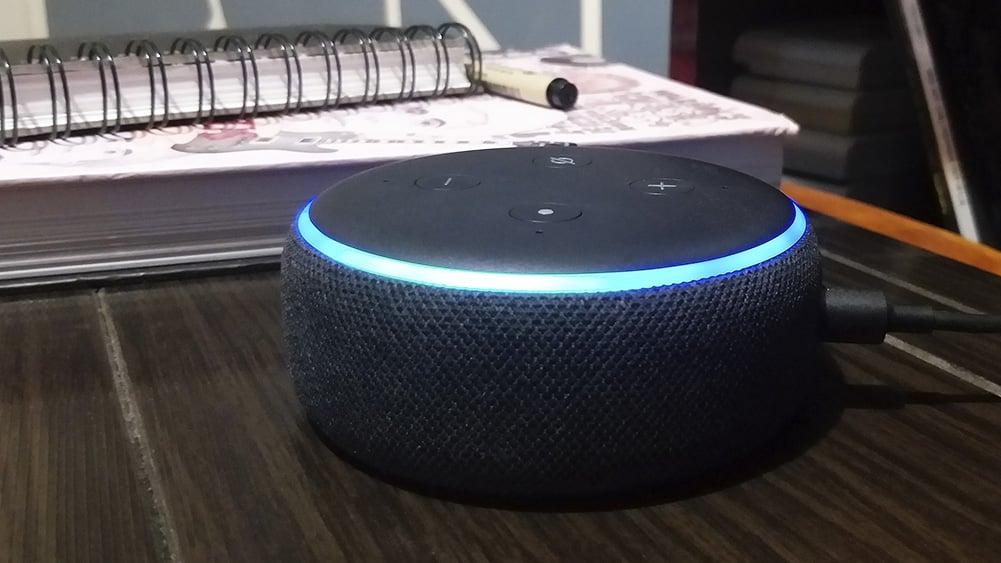 Foto do Echo Dot 3a geração em ciam de uma mesa com agendas ao fundo