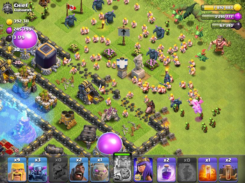 Aplicativo clash of clans, campo de batalha repleto de túmulos, com dragões e tropas de ataque.