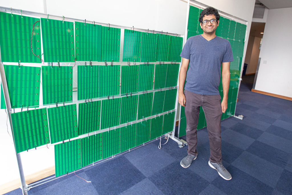 """O líder do projeto da """"superfície inteligente"""", venkat arun, em uma sala ao lado de placas quadradas penduradas em um suporte"""