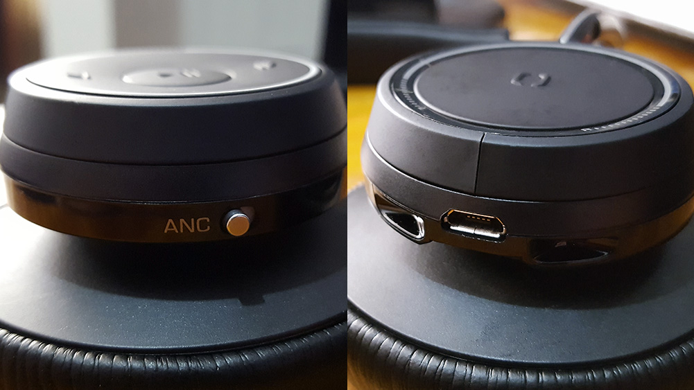 detalhe do switch de boss de baixo e  conexão usb do headset voyager da plantronics, sobre mesa de madeira