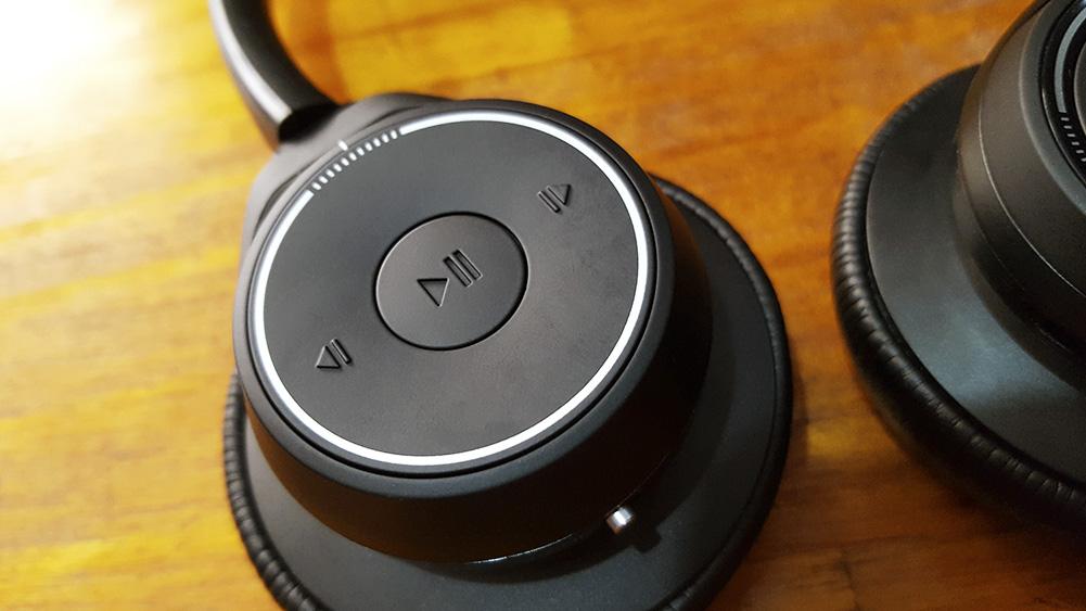 voyager headset da plantronics sobre mesa de madeira com foco nos botões de play/pause e avançar/retroceder música