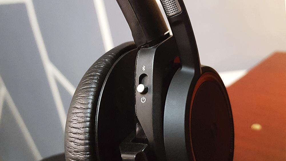 detalhe do switch de bluetooth e ligar/desligar do headset voyager da plantronics, sobre mesa de madeira