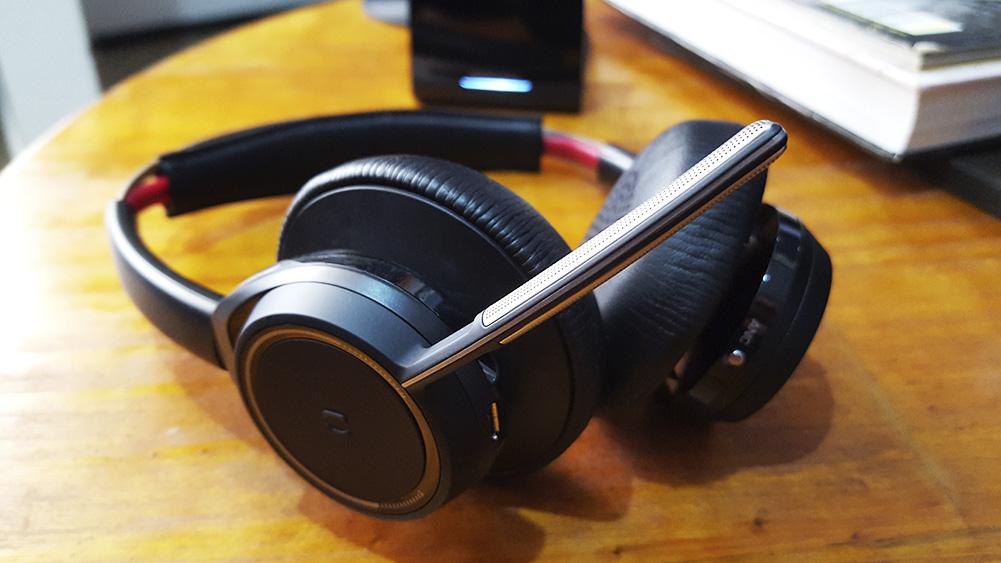 voyager headset da plantronics sobre mesa de madeira com foco no microfone