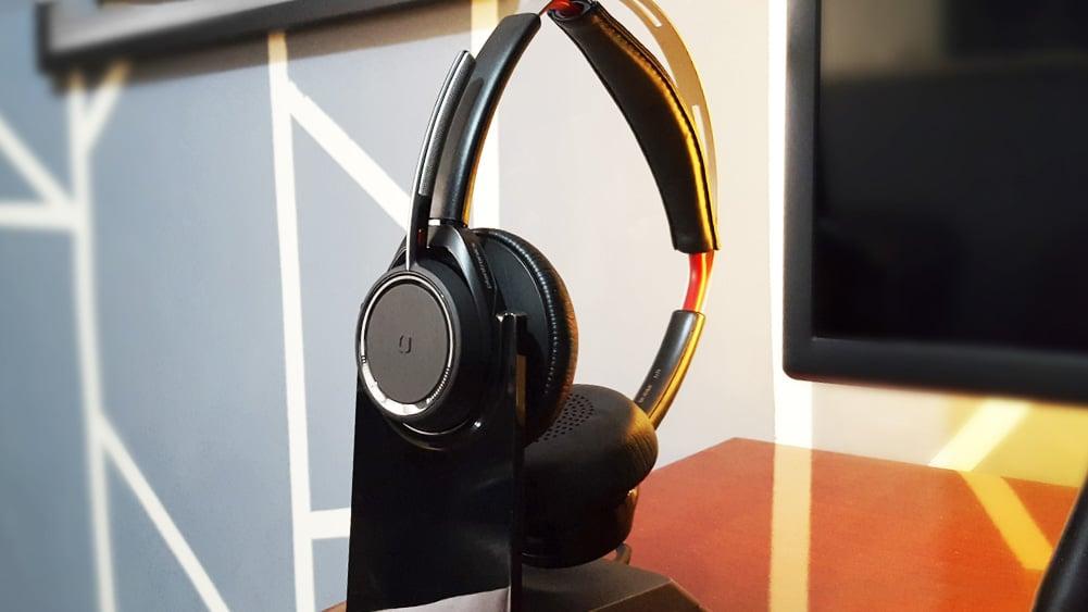 headset da plantronics sobre sua base, em uma mesa de madeira