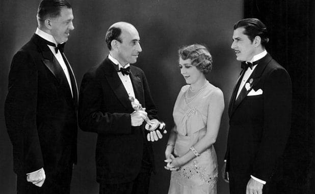 William C Demille, presidente da Academia, entrega um Oscar para Mary Pickford (ao lado de Warner Baxter, na esquerda, e Hans Kraly, direita) na primeira cerimônia de premiação do Oscar.