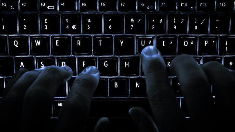 Foto ilustrativa com as mãos de uma pessoa digitando em teclado retroiluminado
