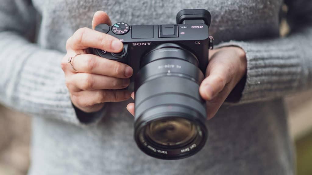 Foco em duas mão de uma pessoa segurando a câmera digital Sony Alpha A6400