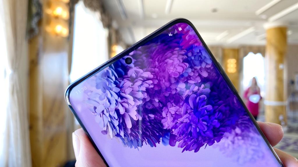 Di bagian atas layar Galaxy S20 +, dengan detail ke kamera, waktu menunjukkan (11:38) dan wallpaper bunga, ungu dan biru.