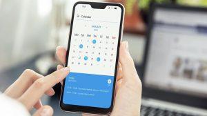 Pessoa checando app do calendário no smartphone para aumentar produtividade