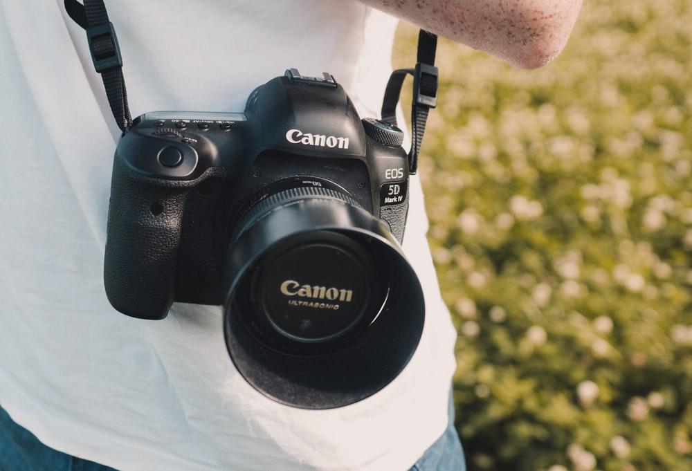A câmera digital Canon EOS 5D está pendurada no pescoço de usuário, ao ar livre