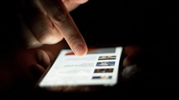 Pessoa clicando numa notícia em um smartphone