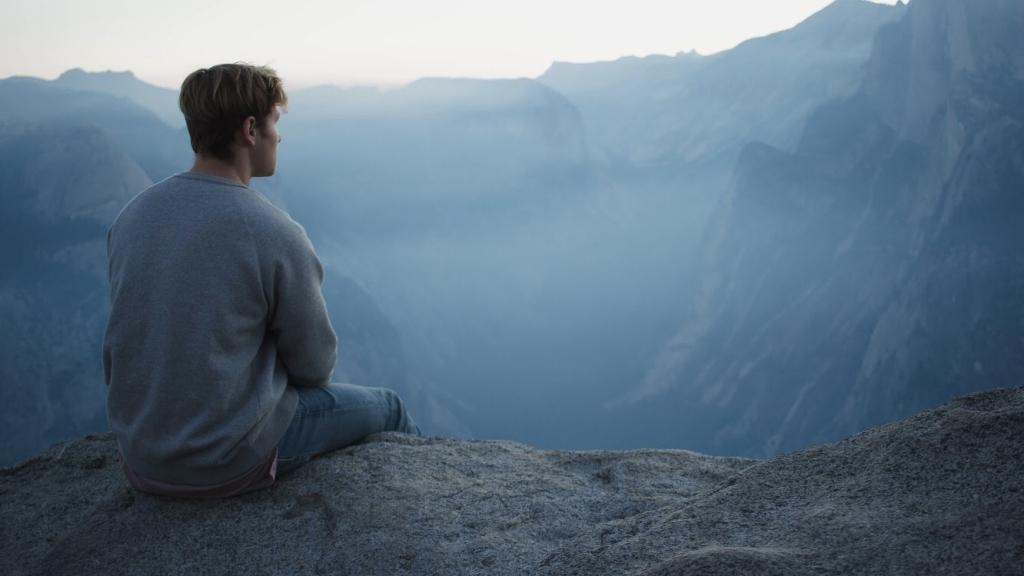 Homem sentado pensativo na beira de um penhasco.