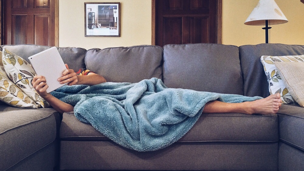 Pessoa debaixo de uma coberta deitada no sofá da sala com tablet nas mãos.
