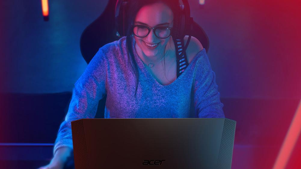 mulher jogando no notebook da dell, usando headphones em ambiente de luz baixa