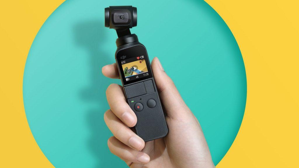 O Osmo Pocket é segurado em anúncio da câmera, frente à fundo colorido