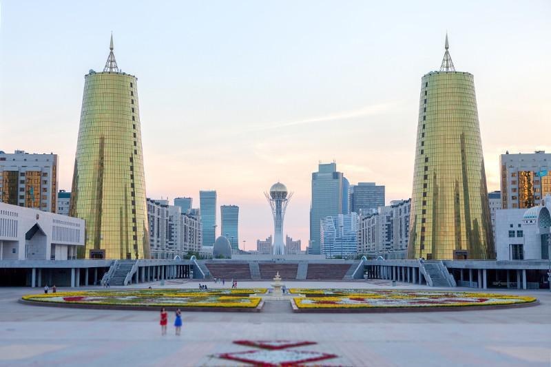 Praça em nursultan, uma das 20 novas cidades do mundo. Ao lado dela, 2 prédios modernos espelhados com visual de cone.