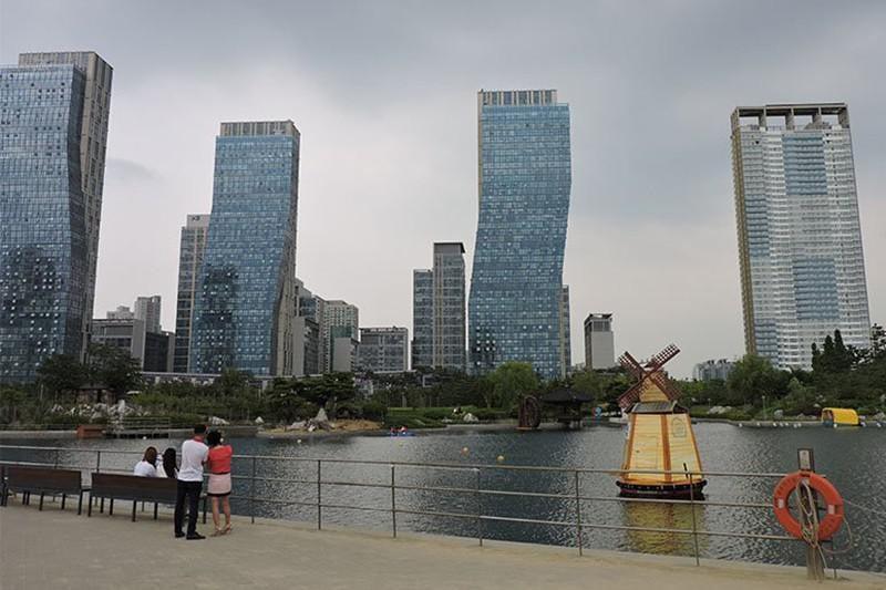 Vários prédios em songdo próximos a um lago. Três deles são tortos, com o topo mais à direita em relação ao solo.