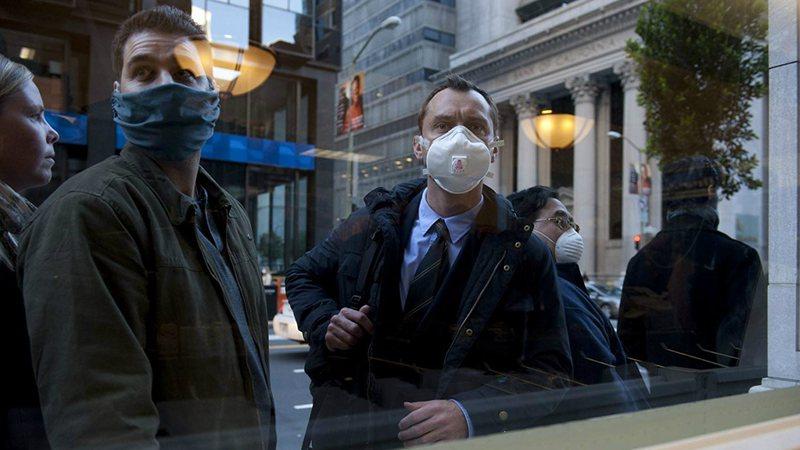 Cena de duas pessoas com máscara no filme Contágio