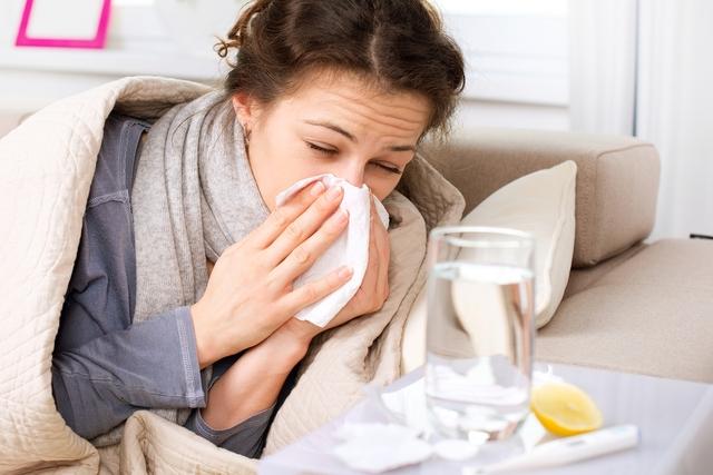 Mulher com gripe segurando um lenço