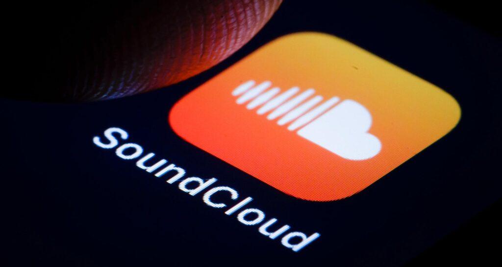 Imagem mostra a ponta de um dedo quase apertando o ícone do app soundcloud em uma tela