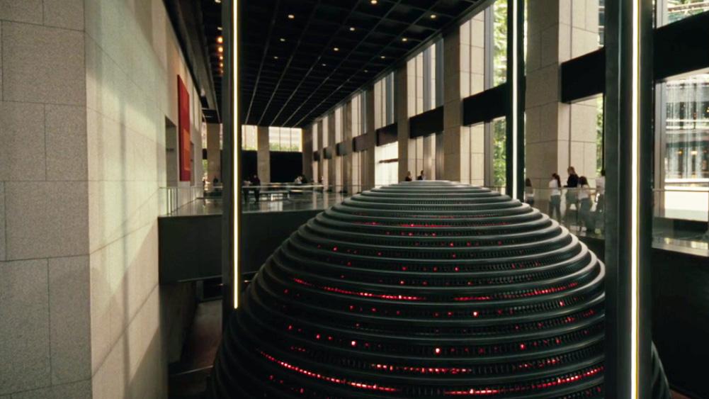 REHOBOAM computador gigante, metálico com luzes vermelhas, dentro de prédio corporativo