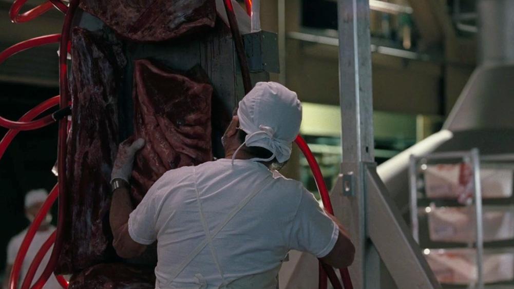 carne impressa em chapa metálica, sendo extraída por um açougueiro