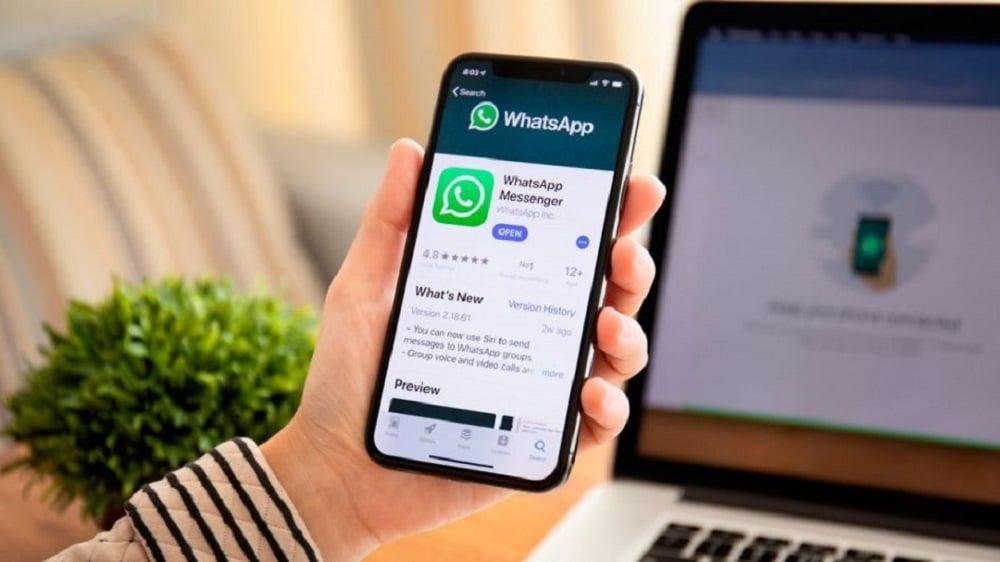 Mão segurando um celular com o app do whatsapp na loja de aplicativos