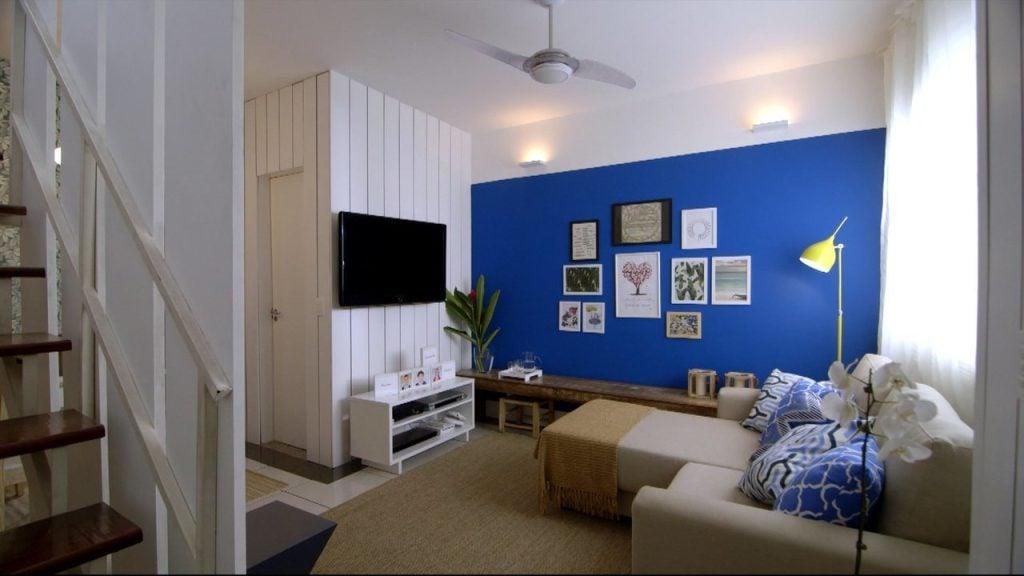 Sala de estar com parede azul e branca, no programa olho mágico - reforma de vizinhos do gnt