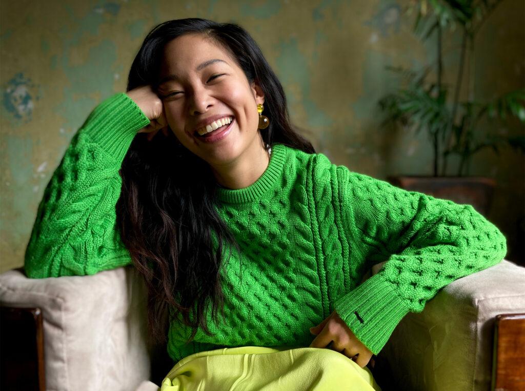 Foto de uma mulher asiática sorrindo tirada com um iphone se 2020. Ela veste um suéter verde de tricô claro e está sentada em uma poltrona cinza.