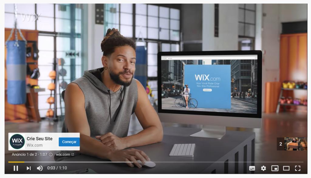 Propaganda da plataforma de criação de sites wix no youtube. Um homem negro está sentado segurando um mouse em frente a  um computador com logotipo do wix na tela
