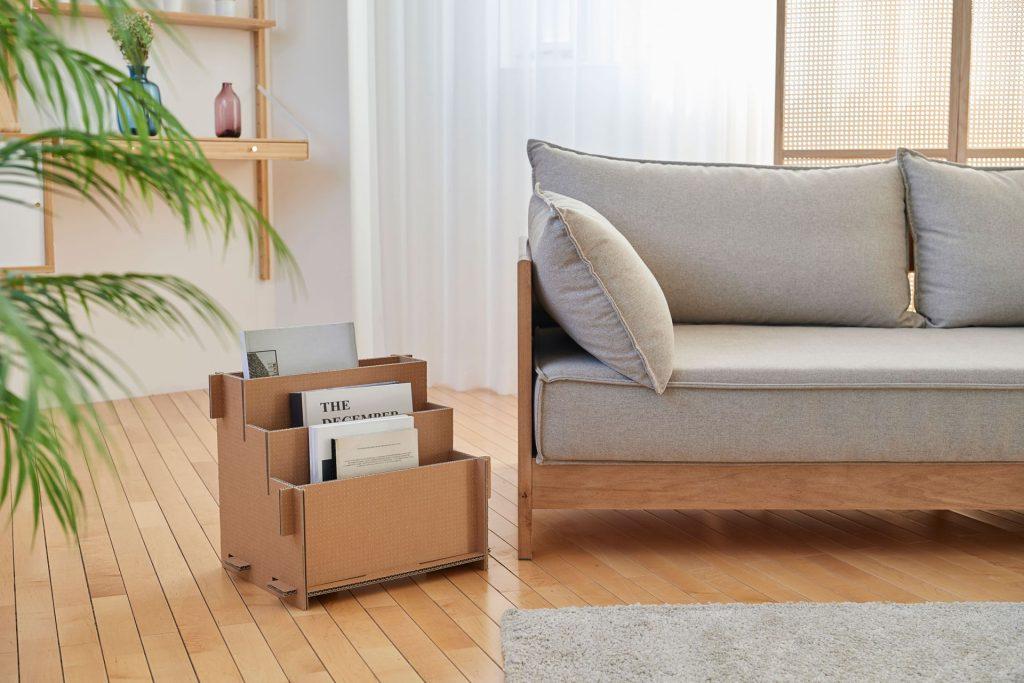 revisteiro ao lado de sofá, piso de madeira e ambiente natural