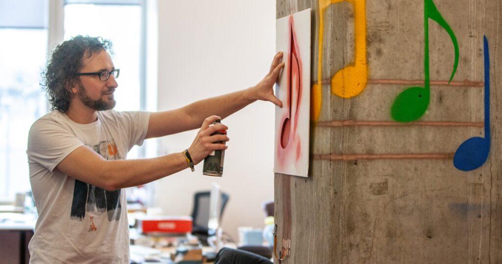 Homem usando o SprayableTech para criar notas musicais em um pilar de concreto